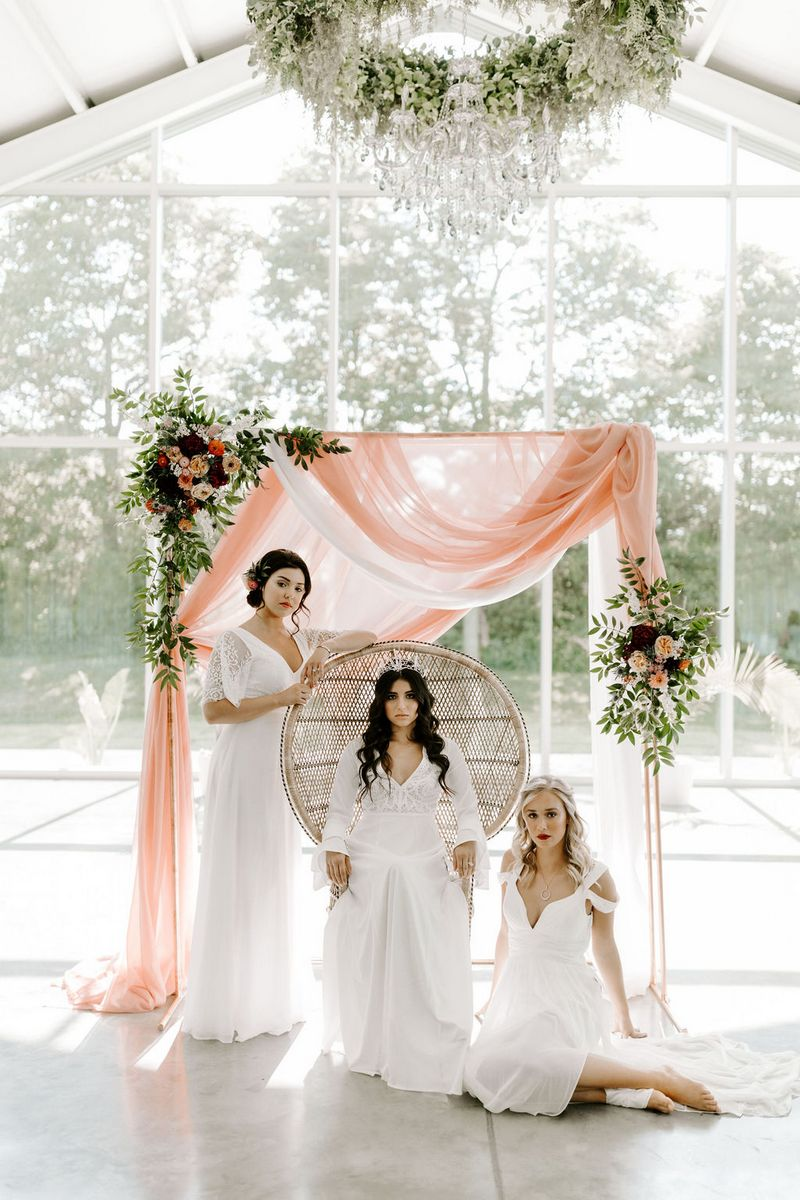 Three brides in front of ceremony backdrop