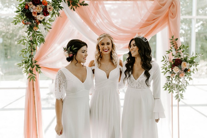 Three brides in front of pink fabric backdrop