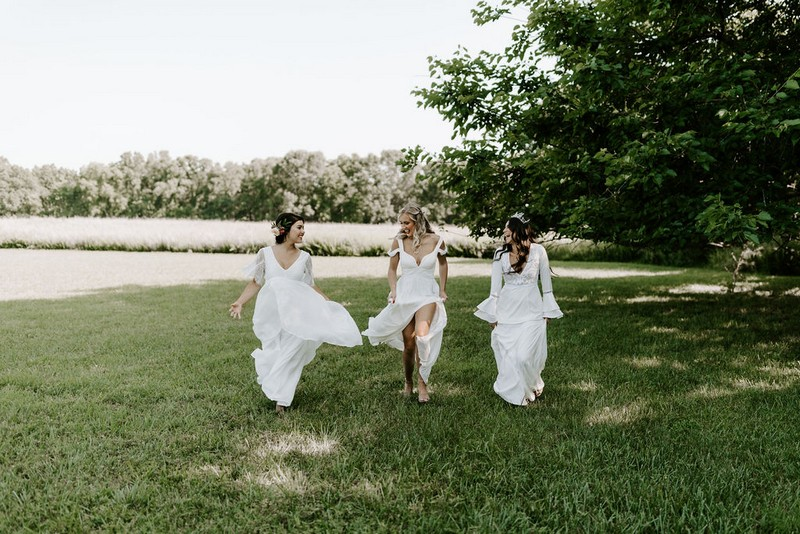 Three brides walking across grass at Greenhouse Two Rivers