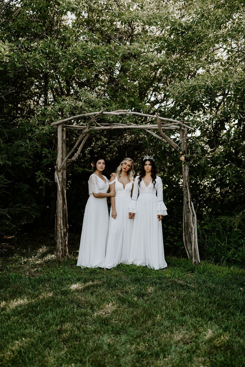 Brides in front of wooden structure in grounds of Greenhouse Two Rivers