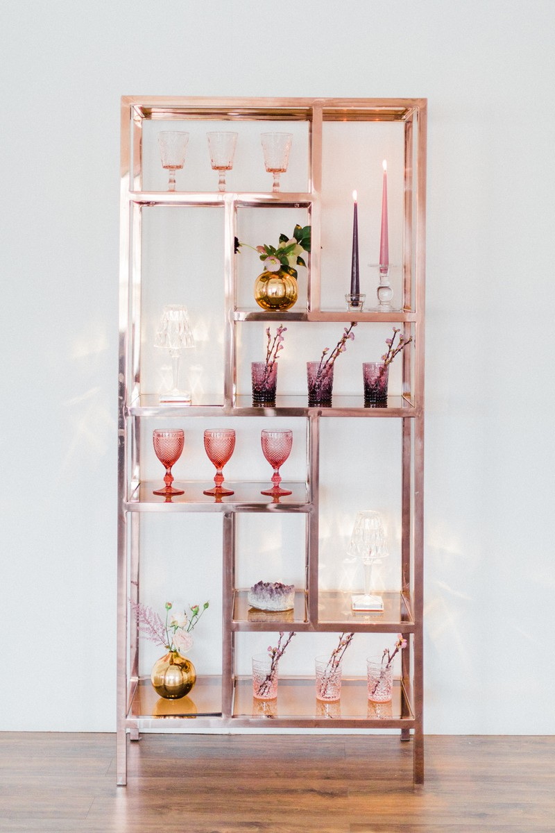 Rose gold shelving unit with styling items for engagement party