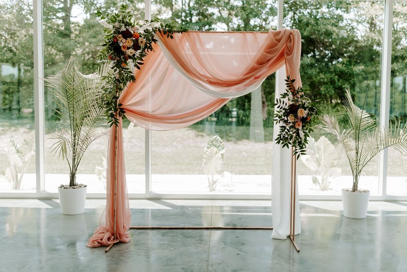 Wedding ceremony backdrop with pink fabric, foliage and flowers