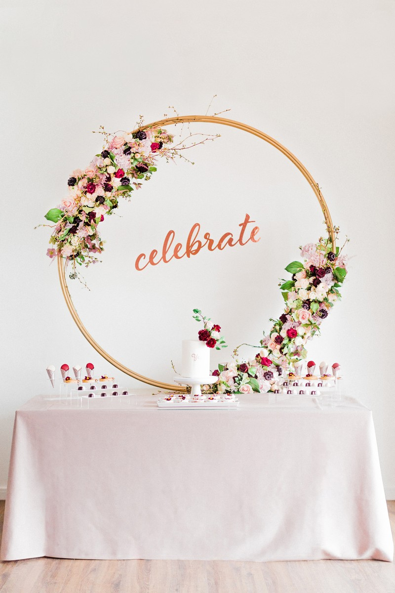 Dessert table for engagement party with large floral hoop and celebrate sign