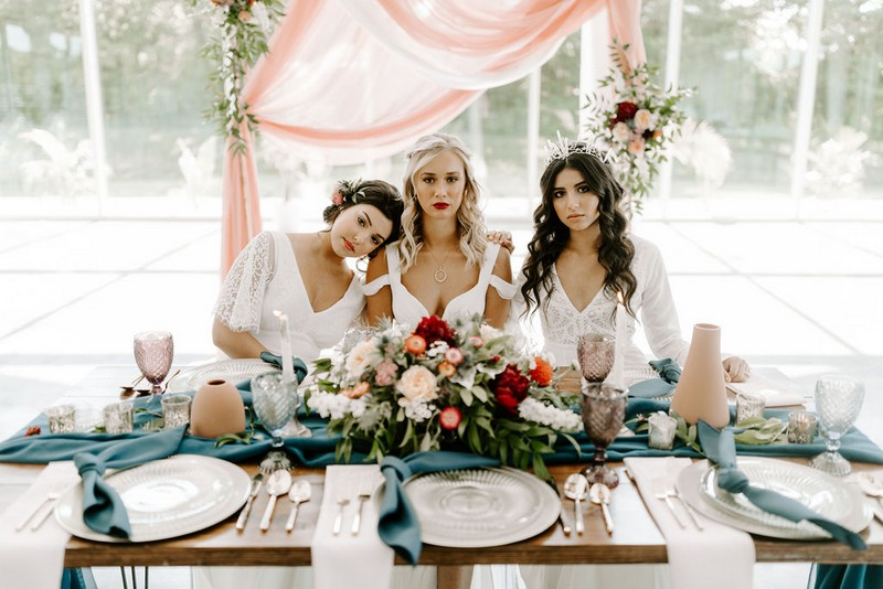 Three brides sitting at winter wedding table with natural styling