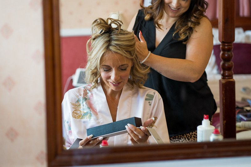 Bride opening gift as she has her hair done