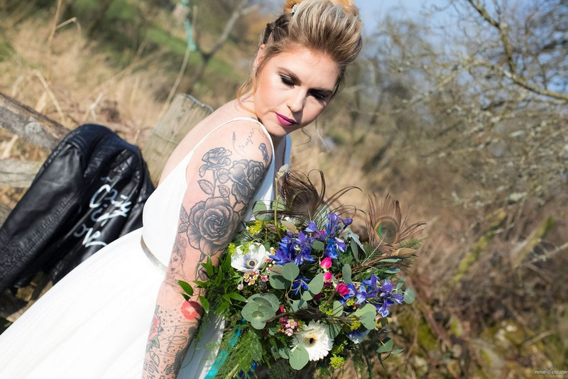 Bride with tattoos on arm holding bouquet
