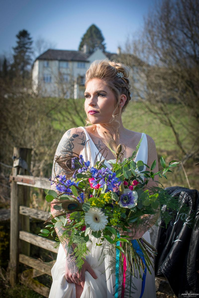 Bride holding rustic bouquet in countryside