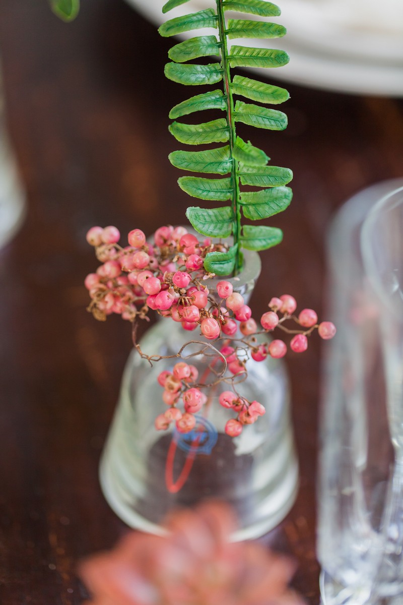 Small red berries in vase on wedding table