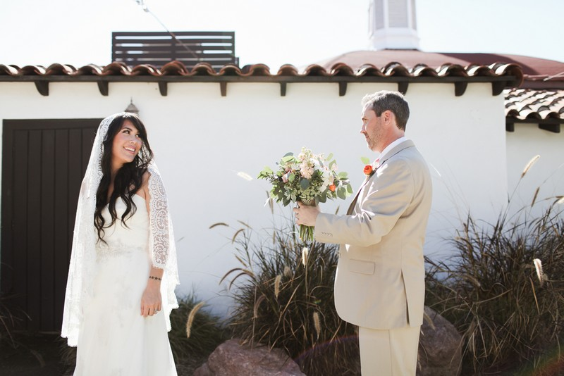Bride turning to see groom holding bouquet