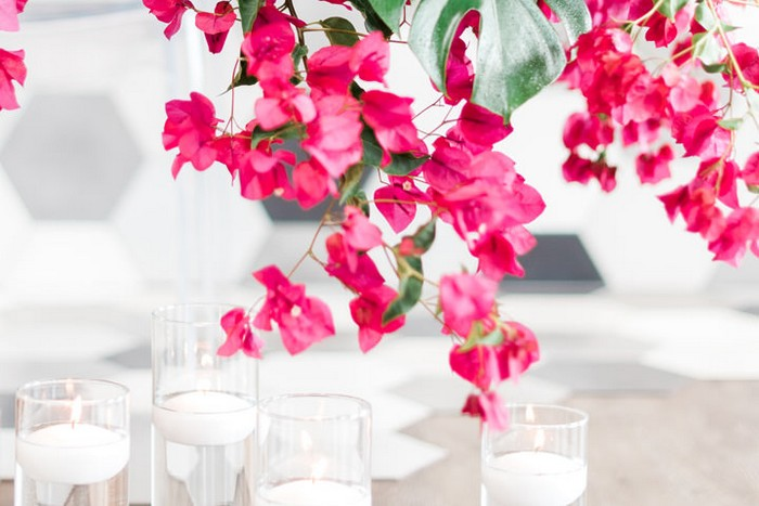 Bougainvillea hanging down over vases of floating candles