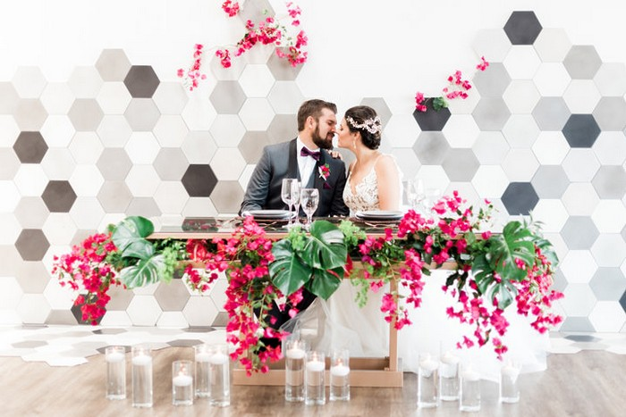 Bride and groom sitting at tropical wedding table styled with bougainvillea