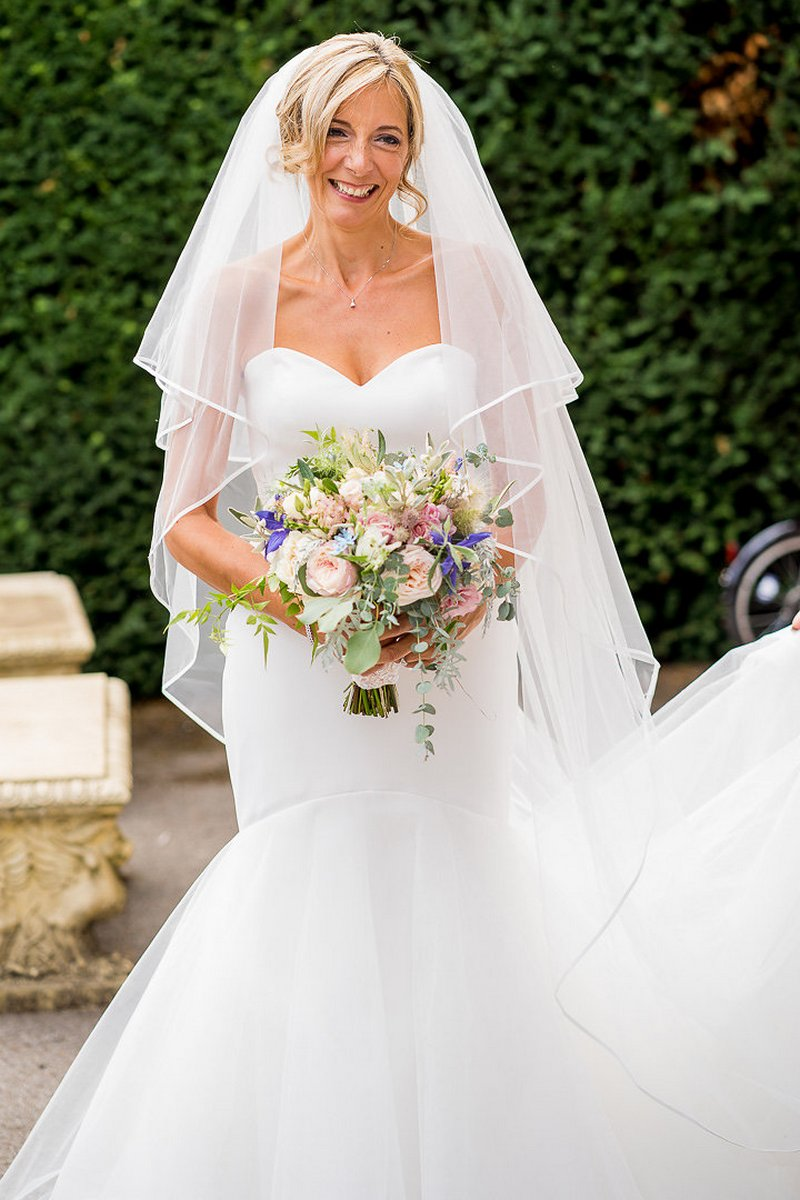 Bride smiling holding bouquet of garden flowers