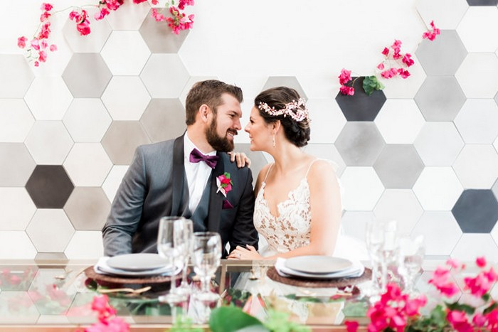 Bride and groom at wedding table in front of hexagonal backdrop