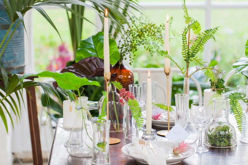 Wedding table styled with tropical leaves, white details and gold candlesticks