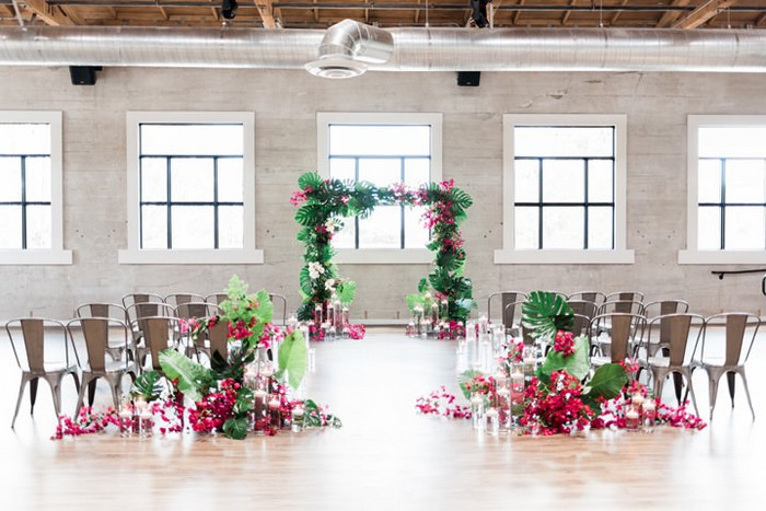 Wedding ceremony arch and seating styled with bright pink bougainvillea and tropical foliage