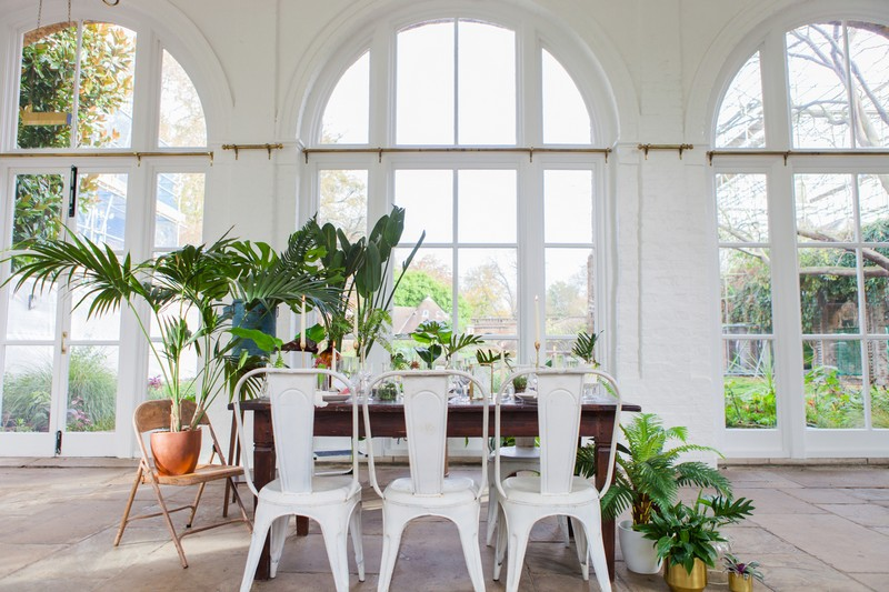 White metal chairs around wedding table with tropical styling