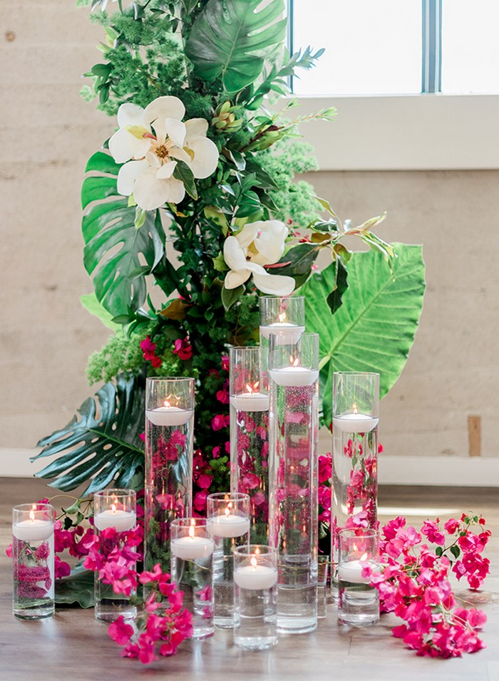 Vases of floating candles in front of tropical palm leaves and bougainvillea