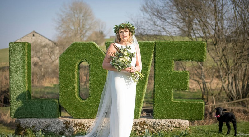 Bride standing in front of green hedge LOVE letters