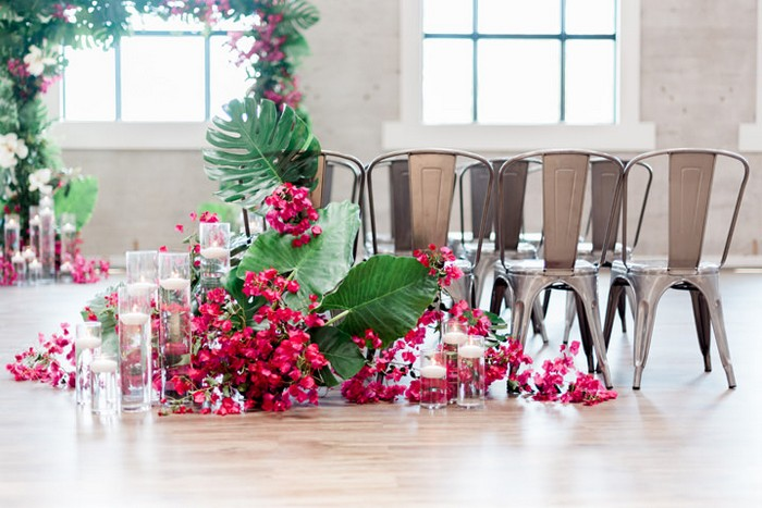 Metal wedding chairs surrounded by tropical palm leaves and pink bougainvillea