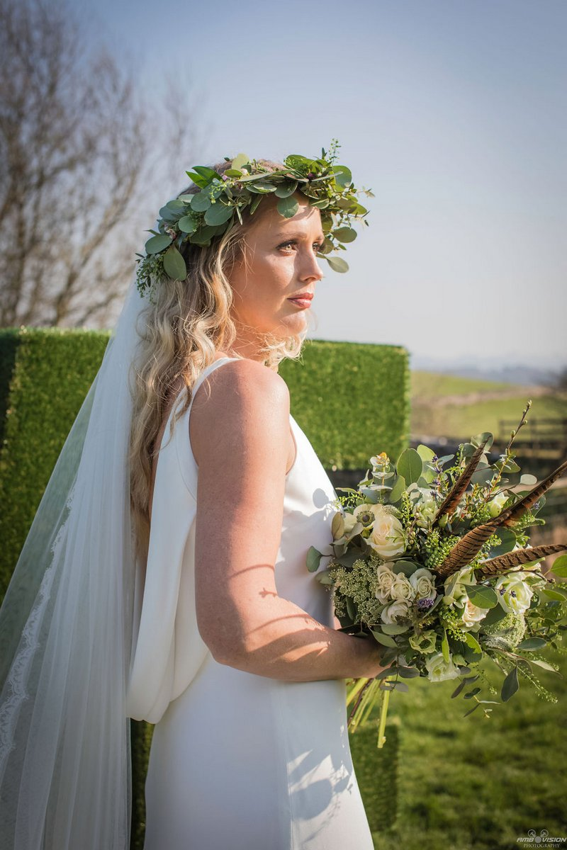 Bride wearing rustic foliage crown and holding bouquet
