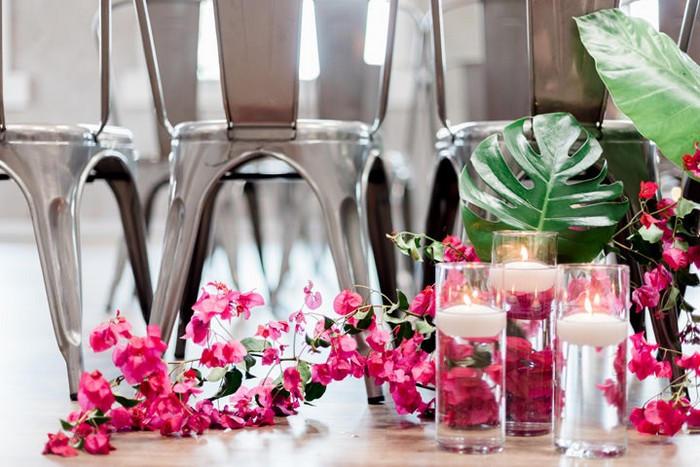 Pink bougainvillea on floor with vases of floating candles