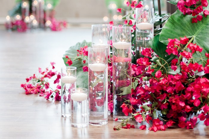 Vases of floating candles with pink bougainvillea and tropical leaves