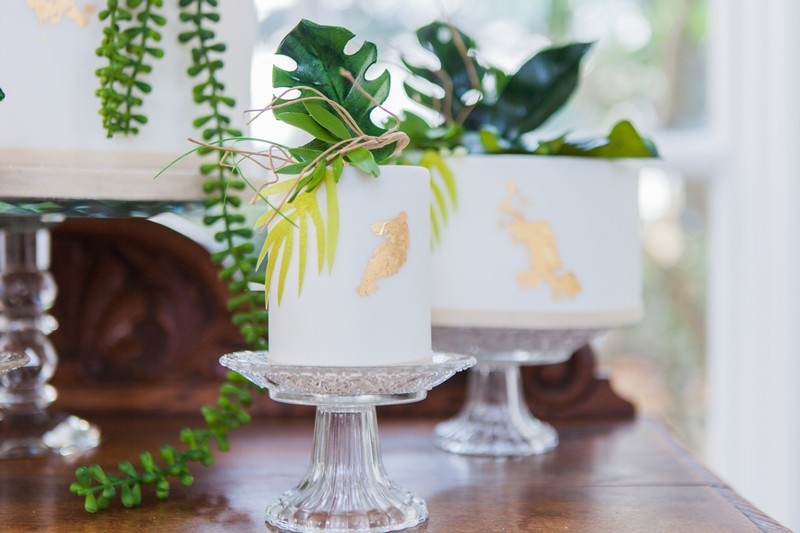 Small white wedding cakes with palm leaf and gold details