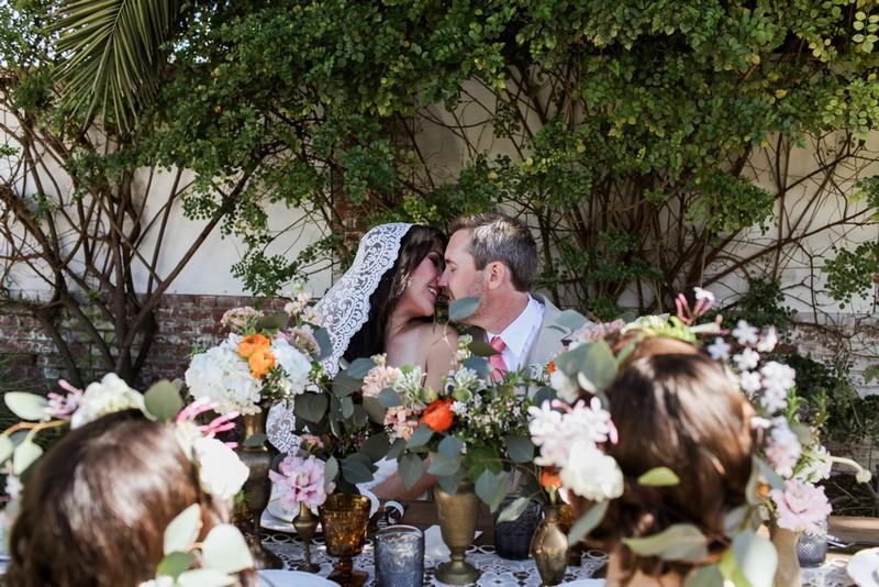 Bride and groom kissing behind wedding table flowers
