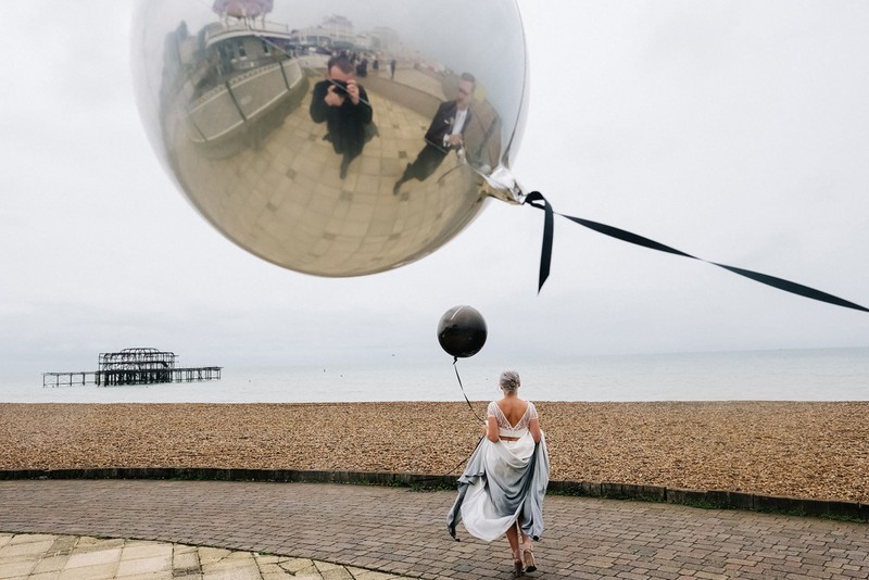 Refelection in balloon of photographer taking picture of bride carrying balloon across seafront - Picture by Kristian Leven Photography