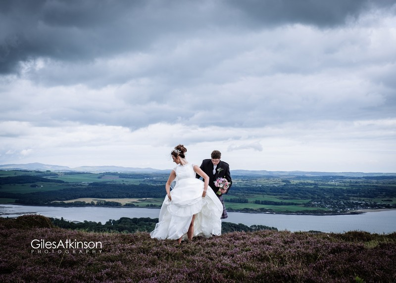 Bride lifting skirt to walk across hill with beautiful view in background - Picture by Giles Atkinson Photography