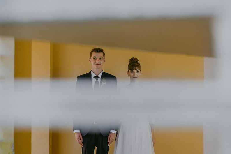 Picture of bride and groom standing next to eash other taken through slats in blind - Picture by Rares Ion