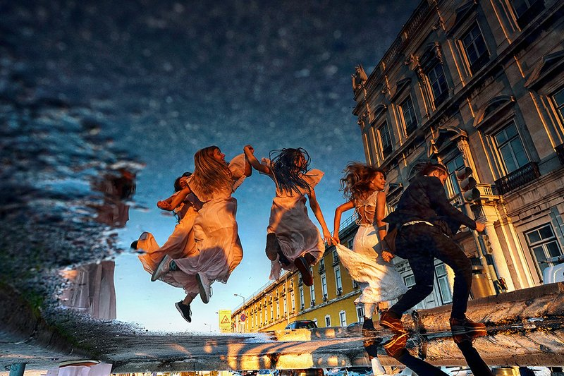 Reflection in puddle of bridesmaids jumping across road - Picture by Emin Kuliyev