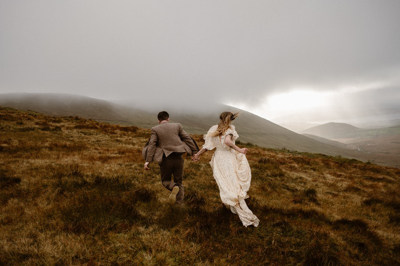 Groom leading bride by the hand across hilltop in clouds - Picture by Larsen Photo Co.
