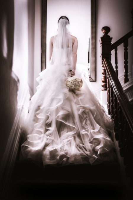Bride walking up staircase - Picture by Peter Rollings Photography