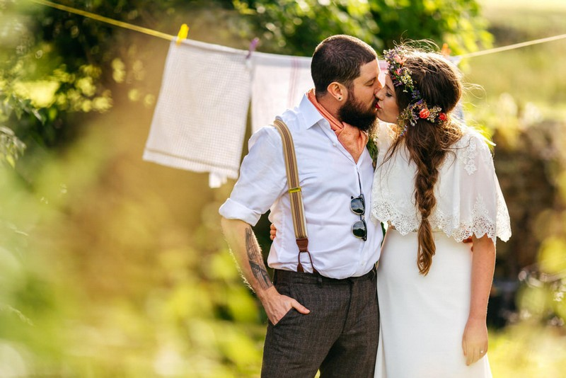 Vintage bride and groom kissing in front of washing line - Picture by Jordanna Marston Photography