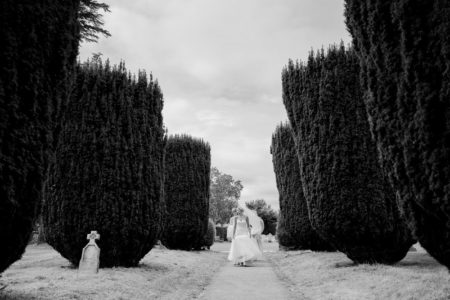 Bride walking down path past bushes to wedding ceremony - Picture by Joss Denham Photography