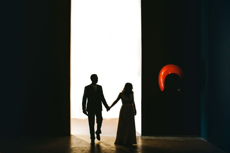 Bride and groom walking through bright doorway into dark room - Picture by Craig Williams Photography