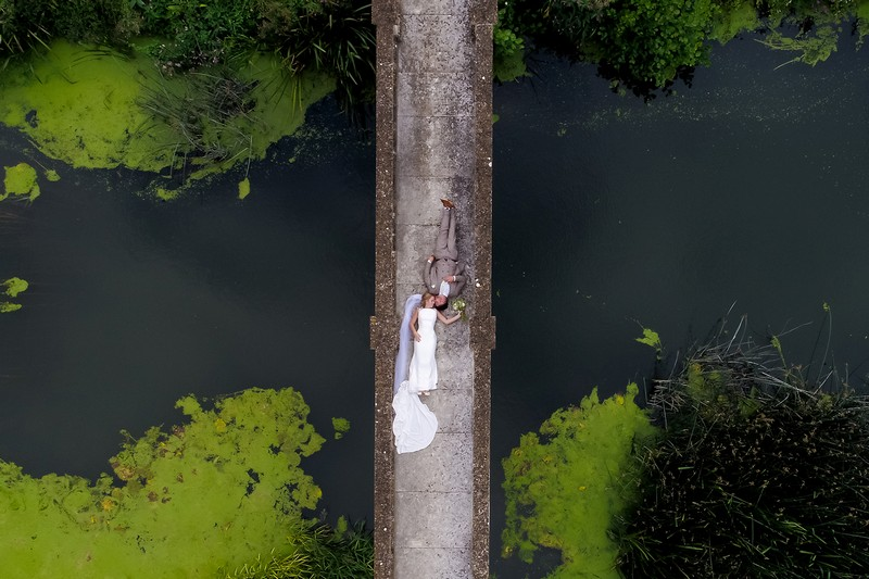 Aerial picture of bride and groom lying down on bridge - Picture by Copper and Blossom