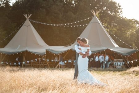 Groom hugging bride from behind in front of tipi - Picture by Penny Young Photography