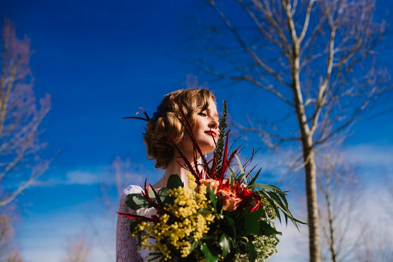 Bride holding bouquet in front of backdrop of blue sky and trees - Picture by Gina Fernandes Photography