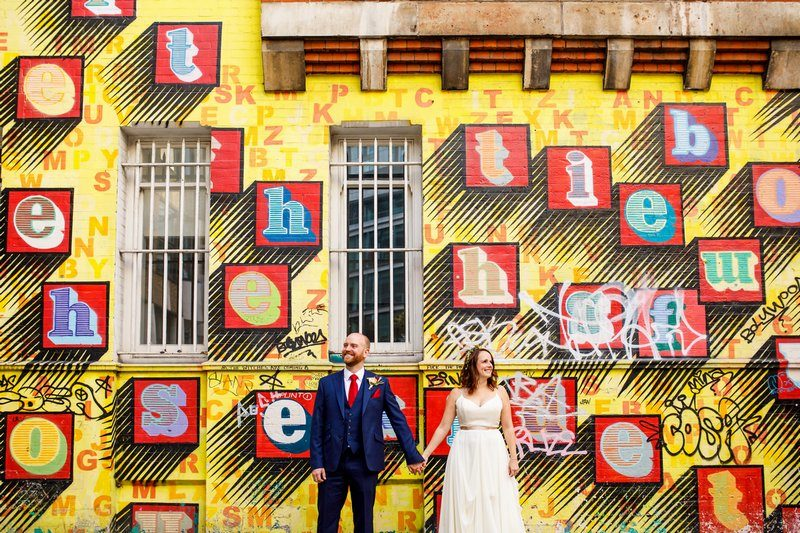 Bride and groom standing in front of wall with Ben Eine graffiti - Picture by John Woodward Photography