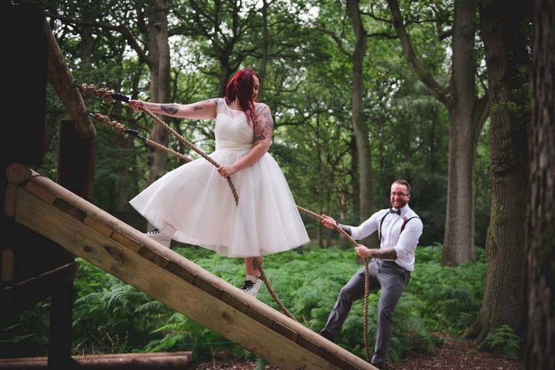 Bride and groom holding onto ropes on assault course obstacle - Picture by Nick Brightman Photography