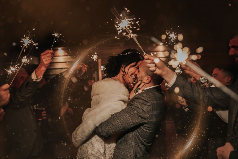 Bride and groom about to kiss surrounded by wedding guests with sparklers - Picture by The Soulcase