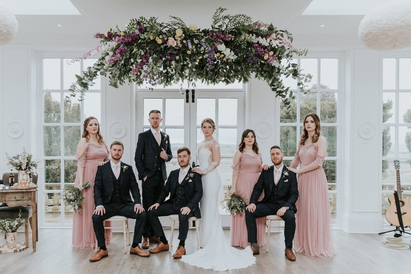 Bridal party posing for photograph under floral chandelier - Picture by Angela Waites Photography