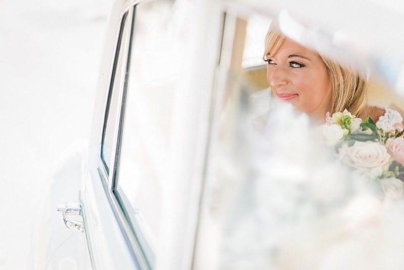 Bride smiling in back of wedding car - Picture by Married to my Camera