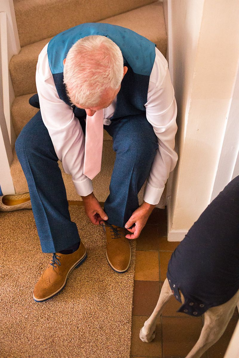 Groom sitting on stairs doing up brown shoes