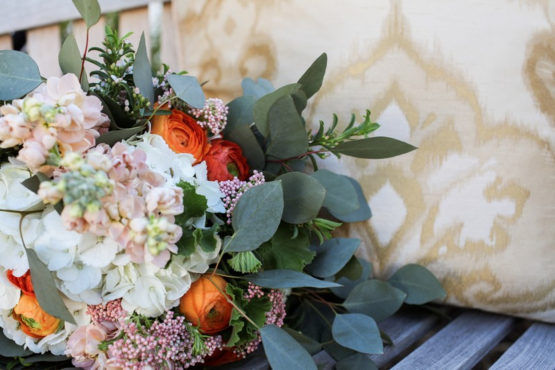 Bridal bouquet with orange and white flowers and green leaves