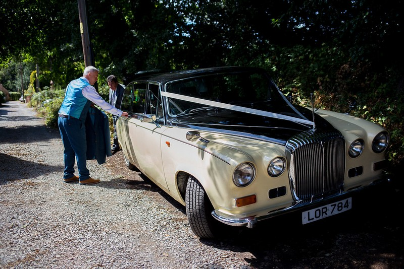 Groom getting into vintage wedding car