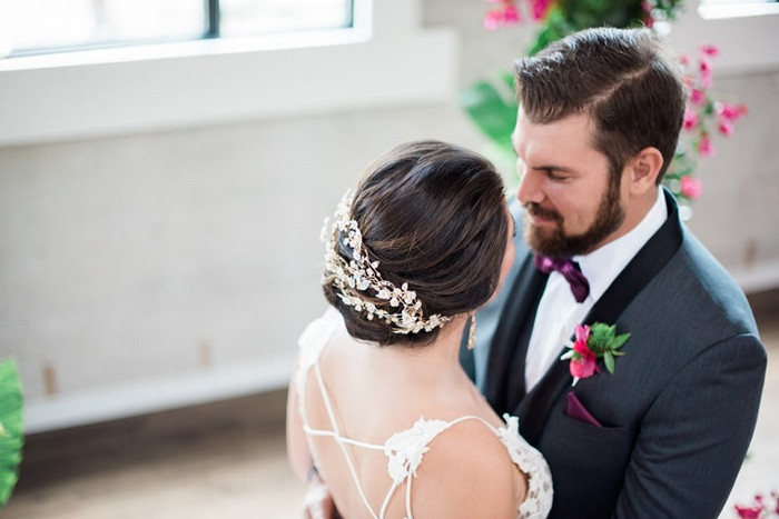 Bride with floral hair accessory facing groom