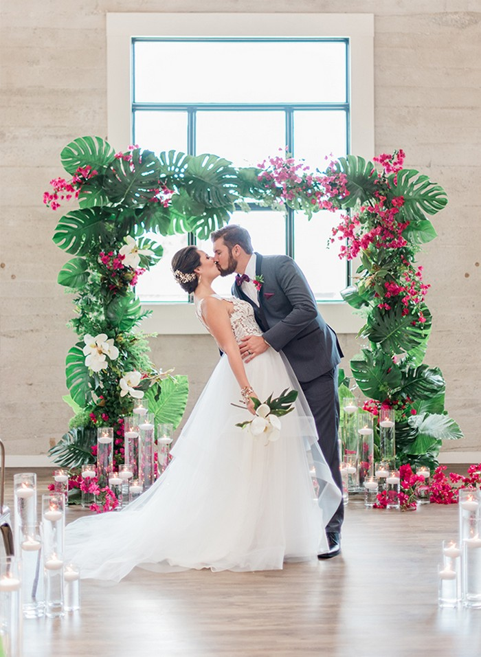 Bride and groom kissing in front of tropical wedding ceremony arch